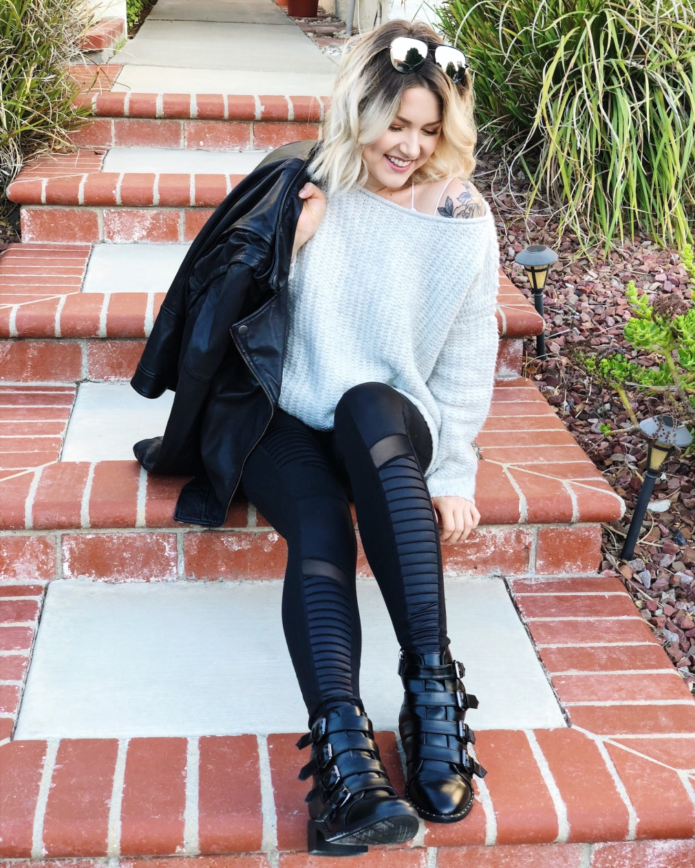 Blonde girl sitting on terra cotta steps, wearing grey off the shoulder sweater, black alo yoga moto leggings and black booties with buckles. She has a leather jacket over one shoulder and quay australia sunglasses on her head.